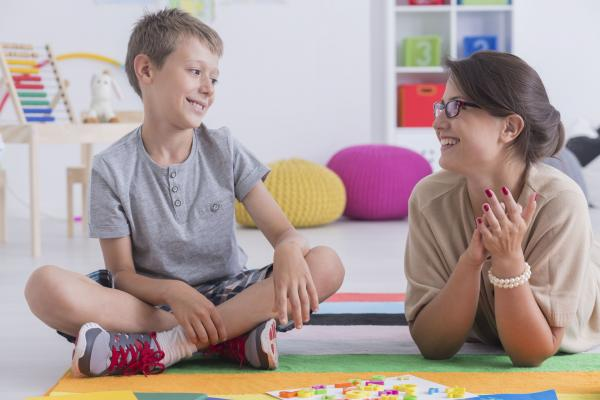 elementary school aged boy sitting with woman and smiling